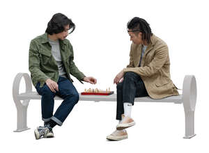two cut out asian men sitting and playing chess in the park