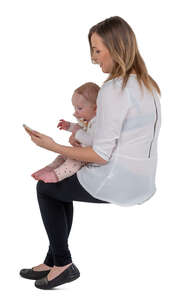 cut out woman holding a baby sitting and making a phone call