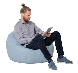 cut out man sitting in a bean bag chair and holding a tablet