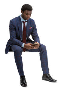 cut out black businessman sitting and texting