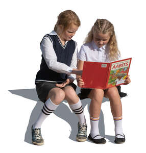 two cut out girls sitting and reading a book