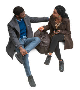 cut out black man and woman sitting and talking seen from above