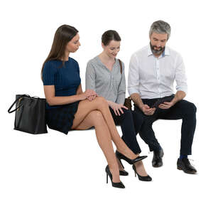 three cut out people sitting and looking at a tablet