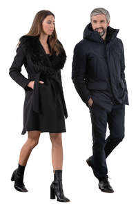 cut out man and woman wearing black overcoats walking