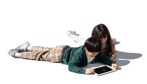 two cut out asian kids lying on the floor and looking at a tablet