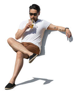 cut out asian man sitting and drinking juice