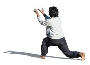 cut out man doing tai chi exercises outside