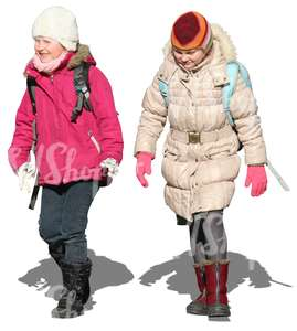two girls with schoolbags walking in winter