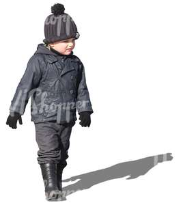 small boy in a black jacket walking