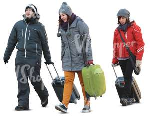 three people carrying suitcases in winter