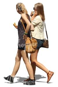 two teenage girls walking and eating an ice cream