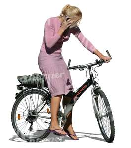 blond woman standing with a bike while on the phone