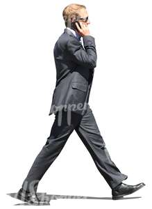 man in a suit walking and talking on the phone