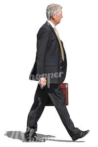older businessman walking with a briefcase in his hand