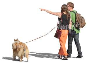 couple walking a dog and pointing at smth