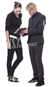 man and a woman standing and looking at the ipad