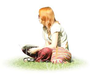 red-haired woman sitting on the grass and reading a book