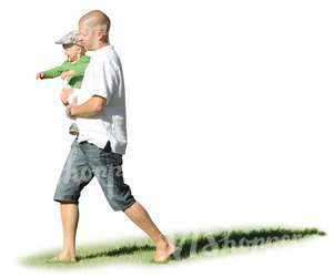 man walking on the grass hoding his son in his arms