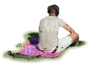 man with headphones sitting in a park on a blanket