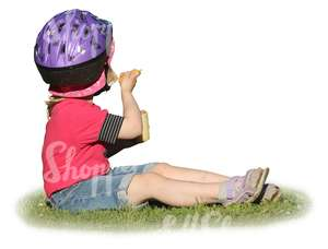 young girl with a helmet sitting on the grass and eating icecream