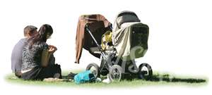 man and woman with a baby carriage sitting on the grass