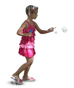 young girl in a pink dress playing with soap bubbles