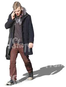 man in a black autumn coat walking and talking on the phone