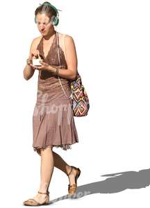 woman with headphones walking and eating icecream