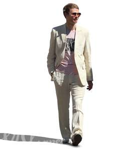 man in a white suit walking and smiling