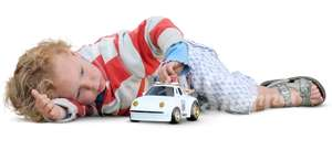 little boy lying and playing with a toy car