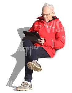 elderly man sitting and reading a tablet