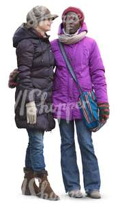 two women in winter clothes standing and talking