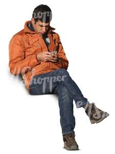 man sitting and looking at his smartphone
