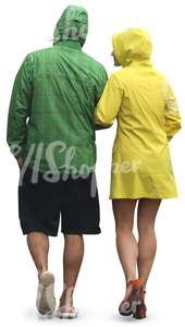 couple in colorul raincoats walking arm in arm