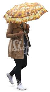 woman in a beige coat walking under an umbrella and listening to music