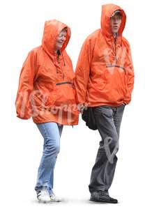 two people in orange raincoats walking hand in hand