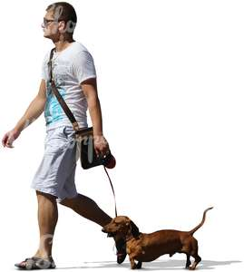 man in white shorts walking a dog