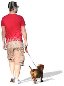 man in a red T-shirt walking a dog