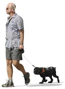 A man walking a black dog