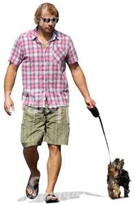 man with sunglasses walking a dog