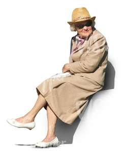 elderly woman in a beige spring coat sitting in the sun