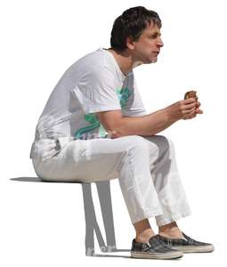 man in white clothes sitting and eating