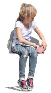 young girl sitting and looking in her handbag