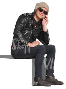 man in a leather jacket sitting and talking on the phone