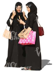 two young arab women in abayas standing and smiling