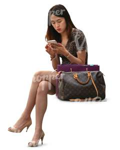 asian woman sitting and looking at her phone