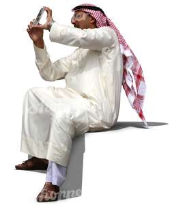 arab man in a thobe sitting and taking a picture