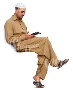 arab man sitting and looking at his phone