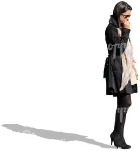 businesswoman in a black coat standing and thinking