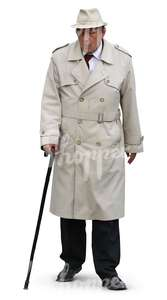 elderly man in a trenchcoat and hat walking